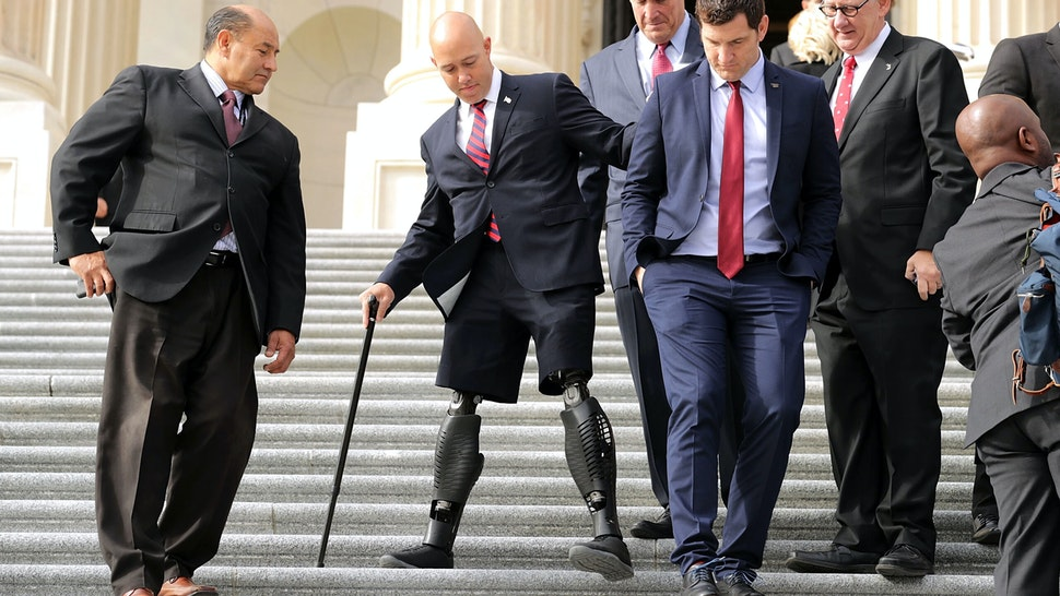 WASHINGTON, DC - NOVEMBER 15: Incoming Republican and Democratic members of Congress, including former U.S. Army Special Operations soldier and Representative-elect Brian Mast (R-FL) (2nd L), walk down the steps of the House of Representatives before posing for a group photograph November 15, 2016 in Washington, DC. There are 50 members of the freshmen class that will join the 115th Congress when it begins in January 2017.
