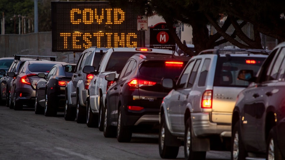 LONG BEACH, CA - December 09: A long line of vehicles line up to take COVID-19 tests at dusk at Long Beach City College-Veterans Memorial Stadium on Wednesday, Dec. 9, 2020 in Long Beach, CA.