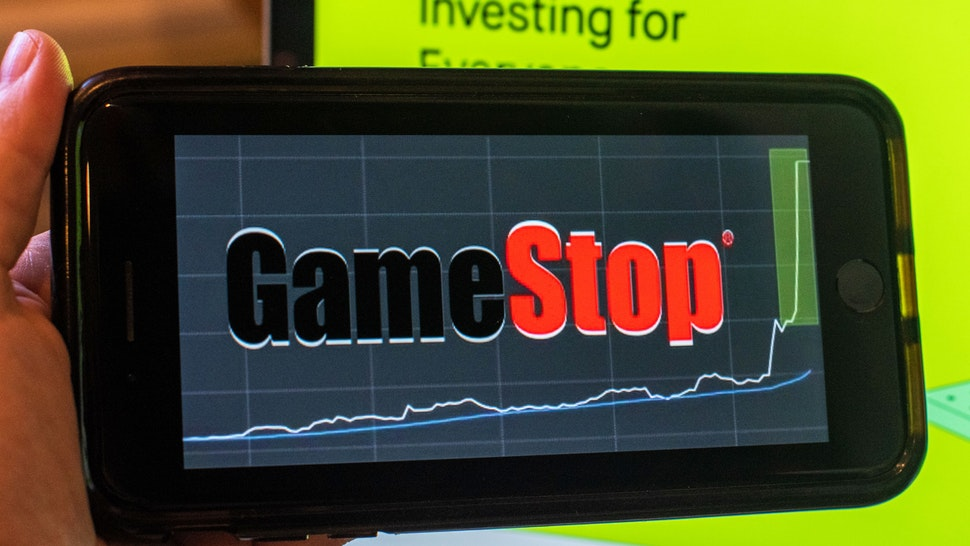 The GameStop Corp. logo on a smartphone and the Robinhood website on a laptop computer arranged in Hastings-On-Hudson, New York, U.S., on Friday, Jan. 29, 2021. GameStop Corp.advanced on Friday and was on track to recoup much of Thursdays$11 billion blowafter Robinhood Markets Inc. and other brokerages eased trading restrictions on the video-game retailer.