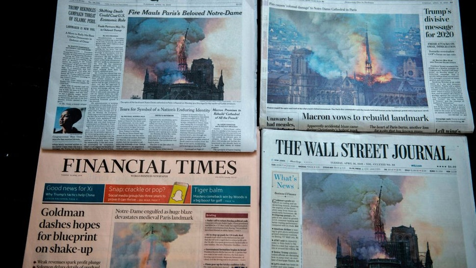The US Newspapers editions of the New York Times, The Washington Post, The Wall Street Journal and the Financial Times display images of Notre-Dame Cathedral burning in Paris on their front page on April 16, 2019 in Washington DC.