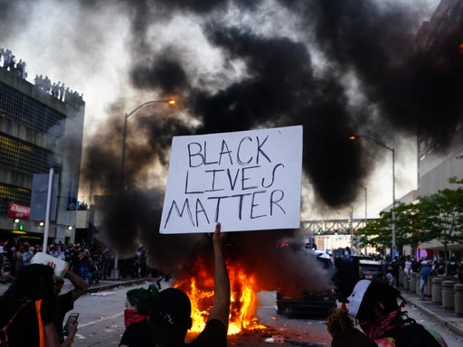 ATLANTA, GA - MAY 29: A man holds a Black Lives Matter sign as a police car burns during a protest on May 29, 2020 in Atlanta, Georgia. Demonstrations are being held across the US after George Floyd died in police custody on May 25th in Minneapolis, Minnesota.