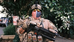 """RICHMOND, VA - JULY 04: A man in full military gear pose for photo holding a gun during an open carry protest on July 4, 2020 in Richmond, Virginia. People attended an event in Virginia tagged """"Stand with Virginia, Support the 2nd Amendment"""". (Photo by Eze Amos/Getty Images)"""