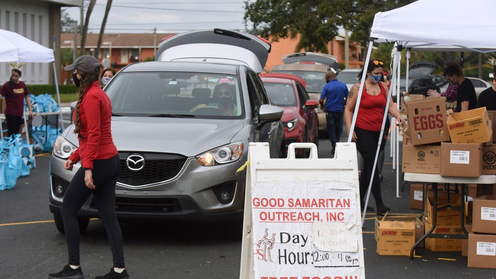 Volunteers load cars with turkeys and other food assistance for laid off Walt Disney World cast members and others at a food distribution event on December 12, 2020 in Orlando, Florida.