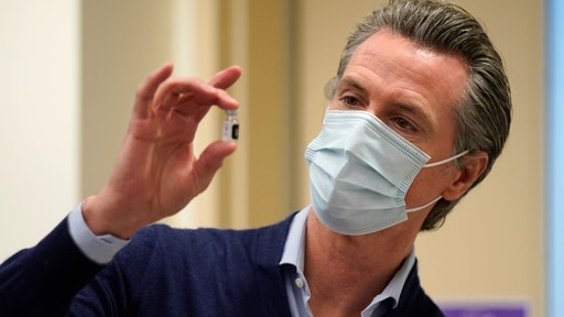 Gov. Gavin Newsom holds up a vial of the Pfizer-BioNTech COVID-19 vaccine at Kaiser Permanente Los Angeles Medical Center on December 14, 2020 in Los Angeles, California.