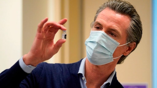 Governor Gavin Newsom holds up a vial of the Pfizer-BioNTech COVID-19 vaccine at Kaiser Permanente Los Angeles Medical Center in Los Angeles, California on December 14, 2020. - The United States kicked off a mass vaccination drive Monday hoping to turn the tide on the world's biggest coronavirus outbreak, as the country's death toll neared a staggering 300,000. (Photo by Jae Hong / POOL / AFP) (Photo by JAE HONG/POOL/AFP via Getty Images)