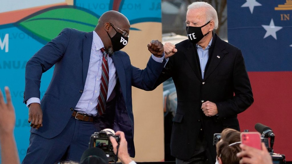 Democratic candidate for Senate Raphael Warnock (L) and US President-elect Joe Biden (R) bump elbows on stage during a rally outside Center Parc Stadium in Atlanta, Georgia, on January 4, 2021