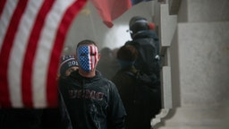 A demonstrator wears an American flag mask during a protest at the U.S. Capitol in Washington, D.C., U.S., on Jan. 6, 2021. The U.S. Capitol was placed under lockdown and Vice President Mike Pence left the floor of Congress as hundreds of protesters swarmed past barricades surrounding the building where lawmakers were debating Joe Biden's victory in the Electoral College. Photographer: Graeme Sloan/Bloomberg via Getty Images