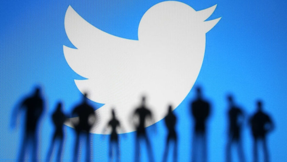 UKRAINE - 2021/01/11: In this photo illustration a Twitter logo is seen displayed in front of the silhouettes of toy people.