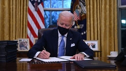 TOPSHOT - US President Joe Biden sits in the Oval Office as he signs a series of orders at the White House in Washington, DC, after being sworn in at the US Capitol on January 20, 2021. - US President Joe Biden signed a raft of executive orders to launch his administration, including a decision to rejoin the Paris climate accord. The orders were aimed at reversing decisions by his predecessor, reversing the process of leaving the World Health Organization, ending the ban on entries from mostly Muslim-majority countries, bolstering environmental protections and strengthening the fight against Covid-19.