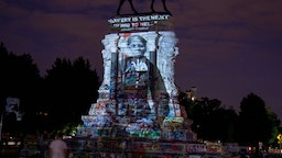 RICHMOND, VIRGINIA - JUNE 18: Harriet Tubman's image is projected on the Robert E. Lee Monument as people gather around on June 18, 2020 in Richmond, Virginia. Richmond Circuit Court Judge Bradley Cavedo ruled on Thursday to indefinitely extended an injunction preventing the Virginia governor from removing a historic statue of Confederate Gen. Robert E. Lee from Richmond's famed Monument Avenue (Photo by Tasos Katopodis/Getty Images)