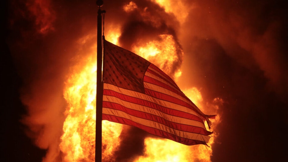 KENOSHA, WISCONSIN - AUGUST 24: A flag flies in front of a department of corrections building after it was set ablaze during a second night of rioting on August 24, 2020 in Kenosha, Wisconsin. Rioting as well as clashes between police and protesters began Sunday night after a police officer shot Jacob Blake 7 times in the back in front of his three children.