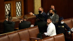 WASHINGTON, DC - JANUARY 06: U.S. Capitol police officers point their guns at a door that was vandalized in the House Chamber during a joint session of Congress on January 06, 2021 in Washington, DC. Congress held a joint session today to ratify President-elect Joe Biden's 306-232 Electoral College win over President Donald Trump. A group of Republican senators said they would reject the Electoral College votes of several states unless Congress appointed a commission to audit the election results. (Photo by Drew Angerer/Getty Images)