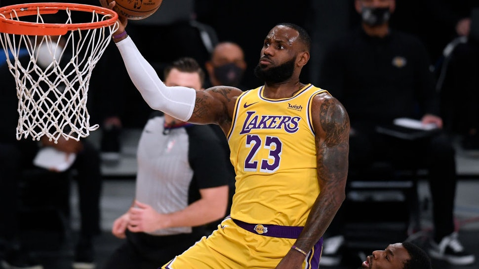 LeBron James #23 of the Los Angeles Lakers scores on a layup past Andrew Wiggins #22 of the Golden State Warriors during the first half at Staples Center on January 18, 2021 in Los Angeles, California.