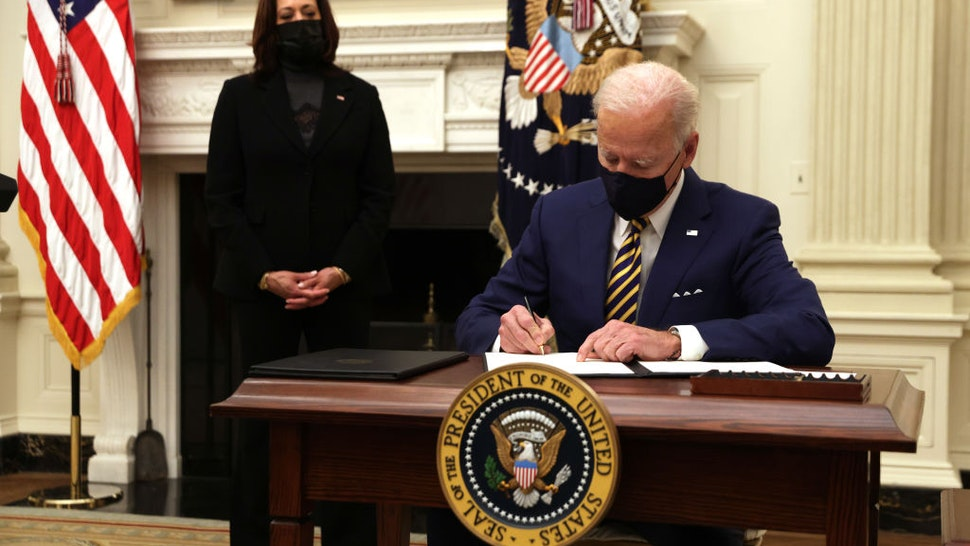 U.S. President Joe Biden signs an executive order as Vice President Kamala Harris looks on during an event on economic crisis in the State Dining Room of the White House January 22, 2021 in Washington, DC.