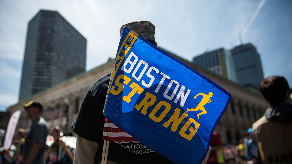 """A soldier in the National Guard with a """"Boston Strong"""" flag cheers on runners as they finish the Boston Marathon on April 21, 2014 in Boston, Massachusetts."""