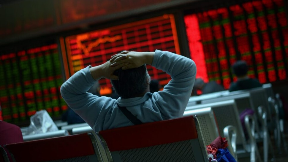 TOPSHOT - An investor looks at screens showing stock market movements at a securities company in Beijing on January 8, 2016. Chinese equities led another day of volatility across Asia on January 8 as investors were panicked by Beijing's attempts to stabilise its beleaguered markets, with fears growing the global economy could be teetering.