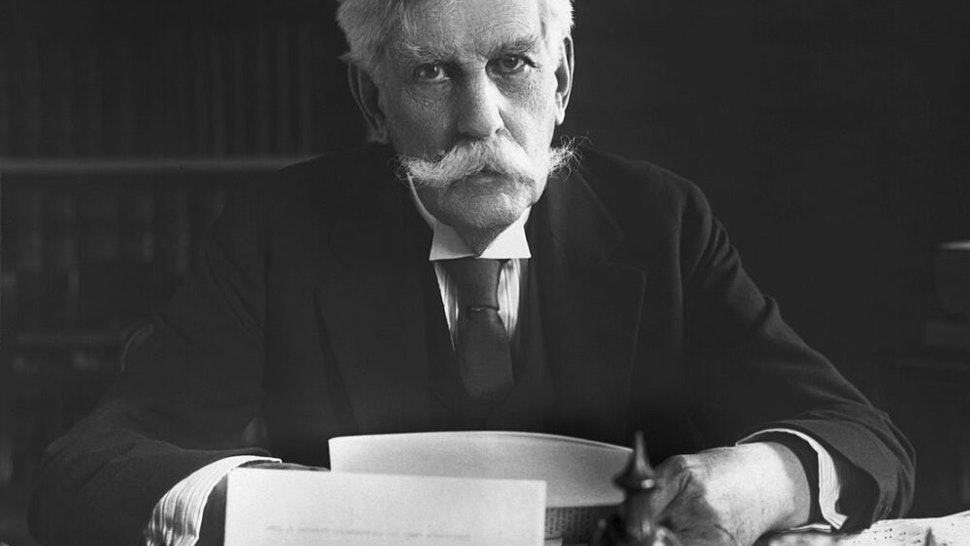 Oliver Wendell Holmes (1841-1935), Associate Justice of the Supreme Court, is shown seated at his desk.