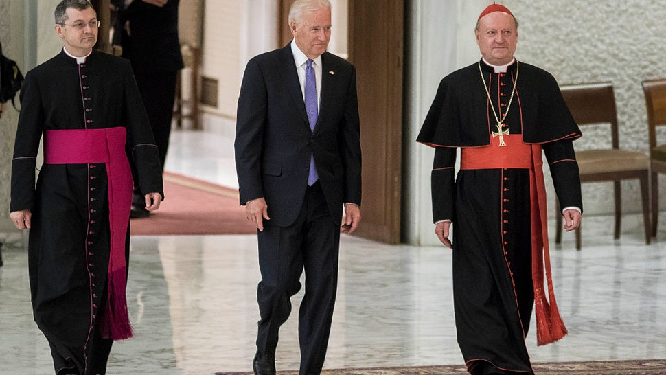 US Vice President Joe Biden (C) is flanked by Cardinal Gianfranco Ravasi (R) as he arrives to attend a special audience celebrates by Pope Francis with participants at a congress on the progress of regenerative medicine and its cultural impact in the Paul VI hall in Vatican City, Vatican on April 29, 2016.(Photo by Giuseppe Ciccia/NurPhoto via Getty Images)