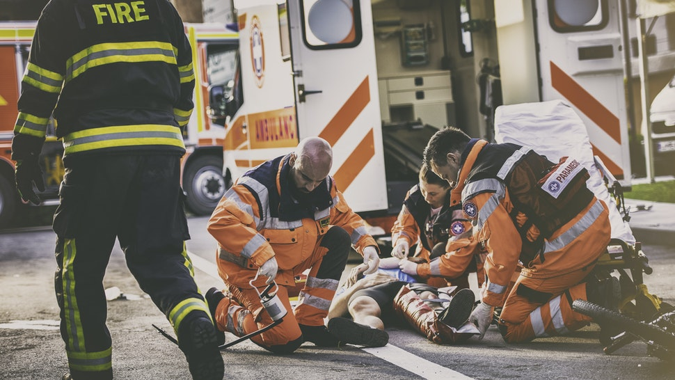 Paramedic team knealing around injured cyclist lying on street, damaged bicycle beside them, firefighter walking past them.