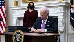 U.S. President Joe Biden signs an executive order after speaking during an event on his administration's Covid-19 response with U.S. Vice President Kamala Harris, left, in the State Dining Room of the White House in Washington, D.C., U.S., on Thursday, Jan. 21, 2021. Biden in his first full day in office plans to issue a sweeping set of executive orders to tackle the raging Covid-19 pandemic that will rapidly reverse or refashion many of his predecessor's most heavily criticized policies. Photographer: Al Drago/Bloomberg