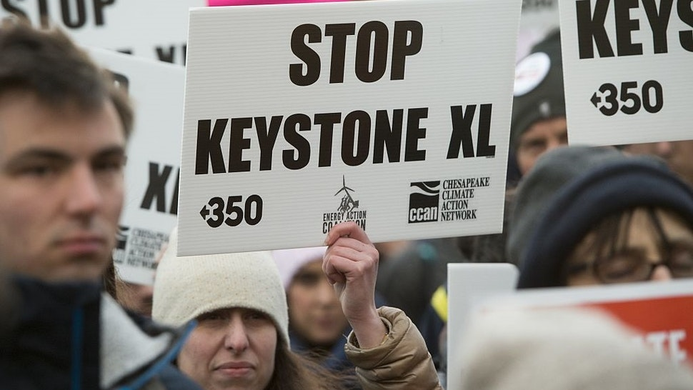Opponents of the Keystone XL and Dakota Access pipelines hold a rally as they protest US President Donald Trump's executive orders advancing their construction, at Lafayette Park next to the White House in Washington, DC, on January 24, 2017.