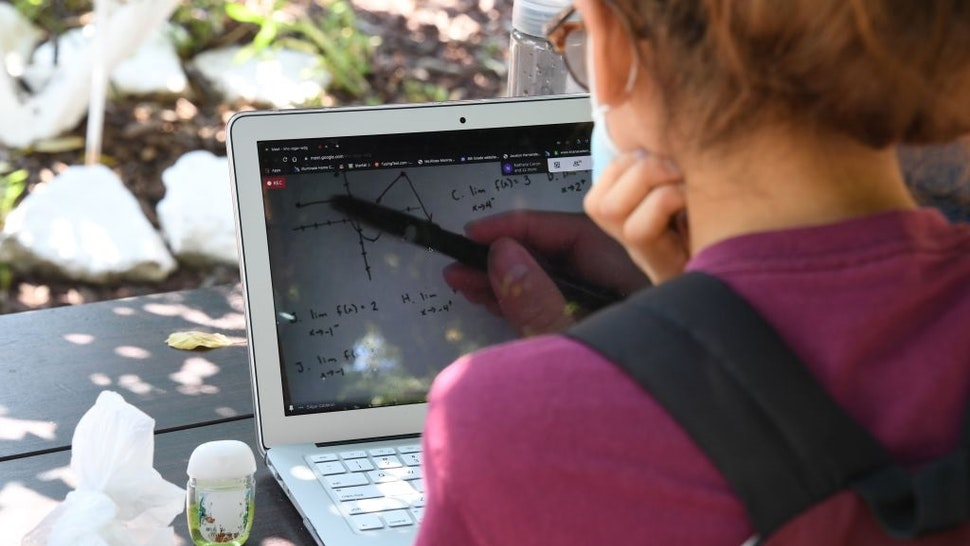 East College Prep High School senior Jocelyn Hernandez follows a remote Advanced Placement (AP) Calculus class while sitting in a community garden near her home, August 14, 2020 in the Boyle Heights neighborhood of Los Angeles, California.