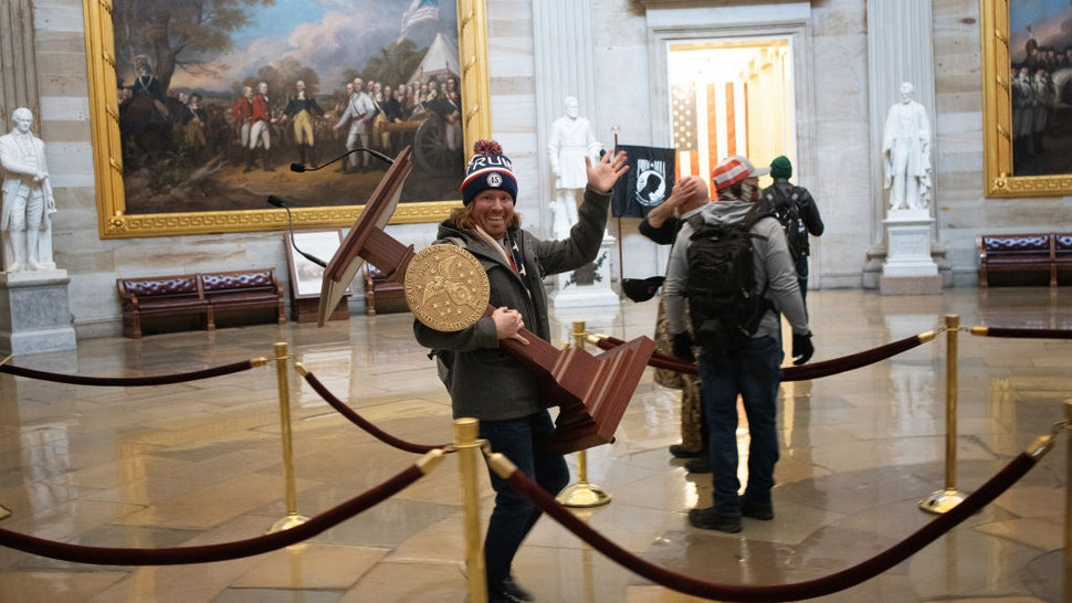 WASHINGTON, DC - JANUARY 06: A pro-Trump protester carries the lectern of U.S. Speaker of the House Nancy Pelosi through the Roturnda of the U.S. Capitol Building after a pro-Trump mob stormed the building on January 06, 2021 in Washington, DC. Congress held a joint session today to ratify President-elect Joe Biden's 306-232 Electoral College win over President Donald Trump. A group of Republican senators said they would reject the Electoral College votes of several states unless Congress appointed a commission to audit the election results.