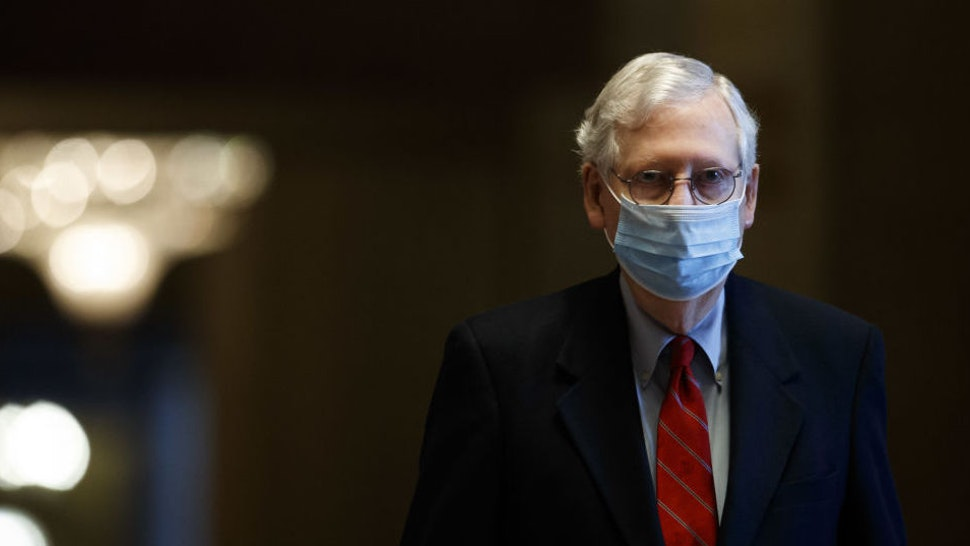 Senate Majority Leader Mitch McConnell, a Republican from Kentucky, wears a protective mask while walking through the U.S. Capitol Building in Washington, D.C., U.S., on Sunday, Dec. 20, 2020. Congressional negotiators cleared the last significant obstacle for pandemic relief legislation with a compromise in a dispute over the future of Federal Reserve emergency lending programs, setting up a possible vote on Sunday.