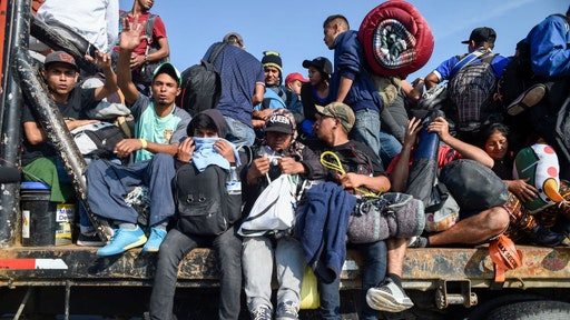 Central American migrants -mostly honduran- taking part in a caravan to the US, get on board a truck heading to Irapuato in the state of Guanajuato on November 11, 2018 after spending the night in Queretaro in central Mexico. - The United States embarked Friday on a policy of automatically rejecting asylum claims of people who cross the Mexican border illegally in a bid to deter Central American migrants and force Mexico to handle them. (Photo by ALFREDO ESTRELLA / AFP) (Photo credit should read ALFREDO ESTRELLA/AFP via Getty Images)