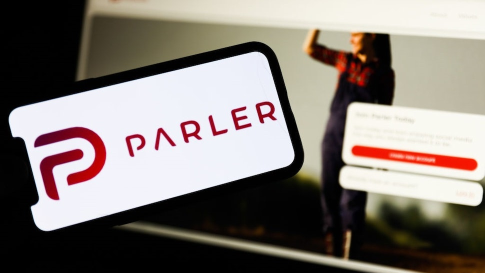 Parler app logo displayed on a phone screen and Parler website displayed on a laptop screen are seen in this illustration photo taken in Poland on January 10, 2020.