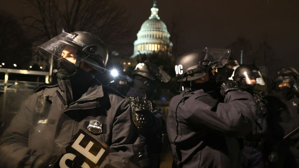 WASHINGTON, DC - JANUARY 06: Police officers in riot gear work to disperse protesters who are gathering at the U.S. Capitol Building on January 06, 2021 in Washington, DC. Pro-Trump protesters entered the U.S. Capitol building after mass demonstrations in the nation's capital during a joint session Congress to ratify President-elect Joe Biden's 306-232 Electoral College win over President Donald Trump.