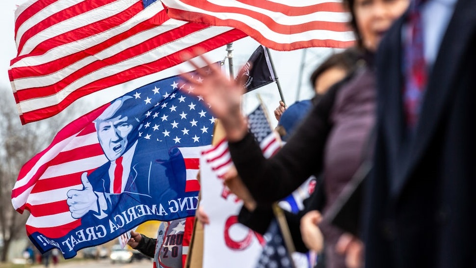 Trump supporters display US flags and signs as the Minnesota chapter of the Council on American-Islamic Relations (CAIR-MN) and a coalition of community organizations in support of Minnesota Representative Ilhan Omar gathered outside the Nuss Truck and Equipment in Burnsville, Minnesota where US President Donald Trump spoke on April 15, 2019.