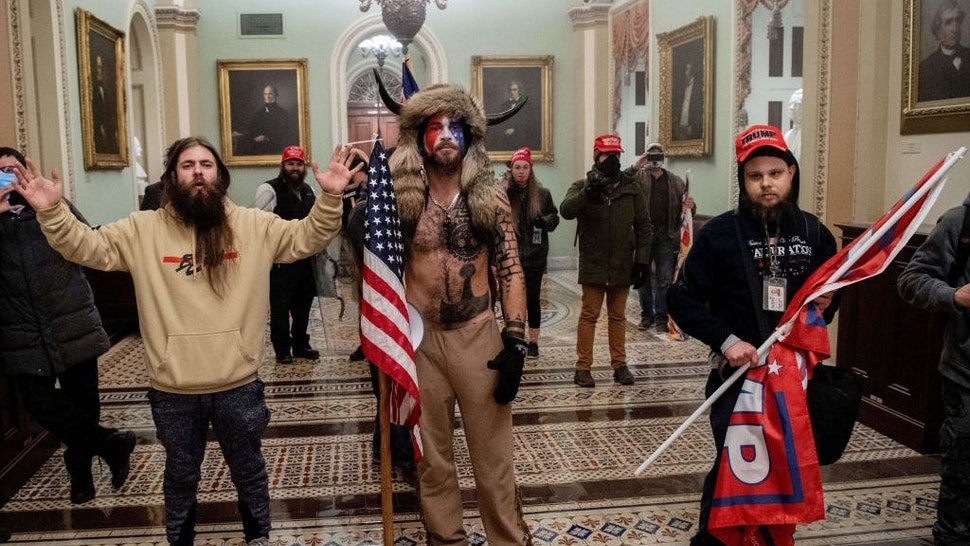 Supporters of US President Donald Trump, including Jake Angeli (C), a QAnon supporter known for his painted face and horned hat, enter the US Capitol on January 6, 2021, in Washington, DC. - Demonstrators breeched security and entered the Capitol as Congress debated the a 2020 presidential election Electoral Vote Certification. (Photo by SAUL LOEB / AFP) (Photo by SAUL LOEB/AFP via Getty Images)