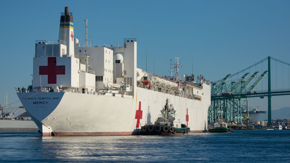Tugboats guide the USNS Mercy hospital ship to moor at the Port of Los Angeles in Los Angeles, California, U.S., on Friday, March 27, 2020.