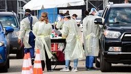 Healthcare personel dressed in personal protective gear help inoculate people arriving to receive Covid-19 vaccines at the Fairplex in Pomona, California on January 22, 2021, one of five mass Covid-19 vaccine sites opened across Los Angeles County this week. - A severely limited supply of Covid-19 vaccines, which only recently became available to the population, could mean people won't be fully inoculated until 2022 unless the supply of the vaccine increases.