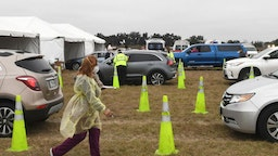 People in cars line up to receive the Moderna COVID-19 vaccine from healthcare workers at a recently opened drive-thru site on January 13, 2021 in The Villages, Florida. The site can accommodate golf carts and will provide up to 800 vaccinations a day to those 65 and older, as well as frontline health care workers.