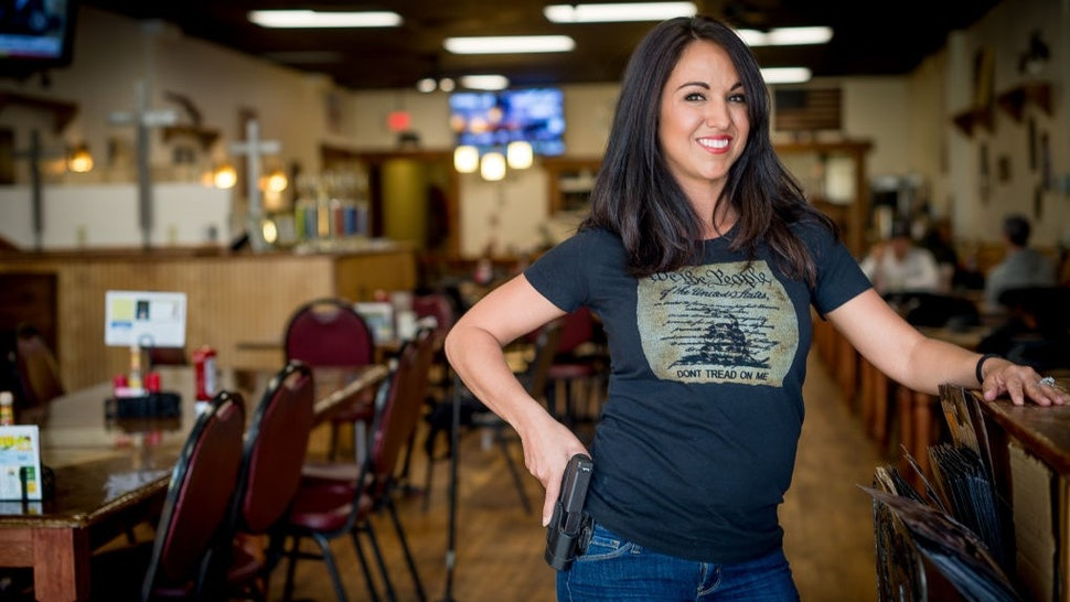 Owner Lauren Boebert poses for a portrait at Shooters Grill in Rifle, Colorado on April 24, 2018. - Lauren Boebert opened Shooters Grill in 2013 with her husband Jason in the small town of Rifle, Colorado, the only city in the United States named after a gun according to them. Shortly after Boebert opened the restaurant, there was a murder in the alley behind it. Boebert went next door to the Tradesmen Gun Store and Pawnshop to speak to the owner, Edward Wilks. Wilks explained to her that you dont need a permit in the state of Colorado to open carry. The next day she started carrying a gun with her. The majority of her staff carries, while it is not a requirement to work there she encourages them to do so if they feel comfortable with it. Customers are also welcome to carry firearms on them as well. The restaurants theme remained heavily country western but revolves alot around the theme of the Second Amendment as well. (Photo by EMILY KASK / AFP) (Photo credit should read