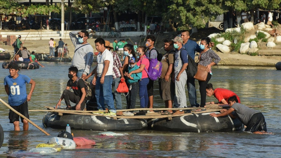 People cross the Suchiate River on a raft from Guatemala to Ciudad Hidalgo, Mexico on January 18, 2021, as a new migrant caravan, mostly of Hondurans heading to the US is expected to arrive. (Photo by ISAAC GUZMAN / AFP) (Photo by