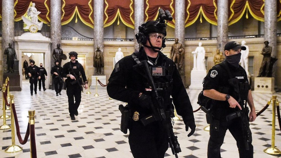 Members of the Swat team patrol and secure the Statuary Hall before US Vice President makes his way into the House Chamber, at the US Capitol, on January 7, 2021 in Washington, DC. - Congress was on track on January 7, 2021 to certify Joe Biden as the next US president and deal a hammer blow to Donald Trump whose supporters stormed the Capitol hours earlier, triggering unprecedented chaos and violence in the seat of American democracy. (Photo by