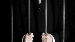 Man in suit behind bars