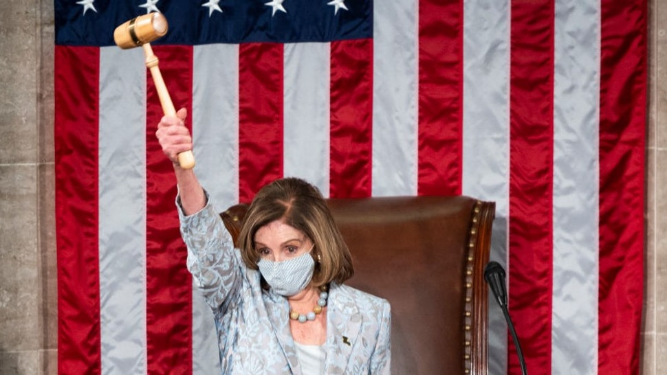 WASHINGTON, DC - JANUARY 3: Speaker of the House Nancy Pelosi (D-CA) holds the Speakers gavel in the air on the House floor in the Capitol after becoming Speaker of the 117th Congress on January 3, 2021 in Washington, DC. Both chambers are holding rare Sunday sessions to open the new Congress on January 3 as the Constitution requires. (Photo By