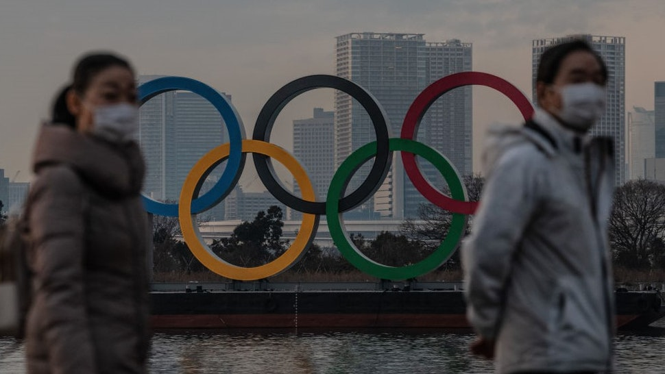 TOKYO, JAPAN - JANUARY 22: People wearing face masks walk past the Olympic Rings on January 22, 2021 in Tokyo, Japan. With just six months to go until the start of the Games, it has been reported that the Japanese authorities have privately concluded that the Olympics could not proceed due to the ongoing Covid-19 coronavirus pandemic. Spokesmen from the IOC and Japanese government have since rejected the report. (Photo by