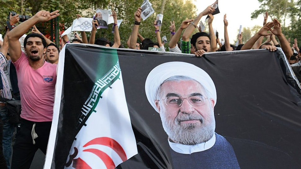 Youth supporters of Hasan Rouhani carry a huge banner with his photo imprinted on it three days prior to his presidential victory during a march on the street on June 12, 2013 in Tehran, Iran. On June 15th Rouhani's presidency was confirmed and announced by Iranian authorities. (Photo by