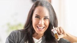 Young woman sprays a nasal bottle spray into the air.