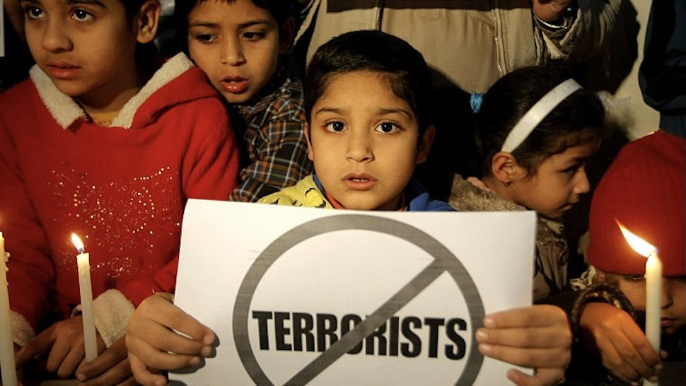 PESHAWAR, Dec. 16, 2015-- Pakistani children hold candles during a vigil to pay tribute to the victims of the Peshawar school massacre in Lahore, eastern Pakistan, on Dec. 15, 2015. Pakistan observed the first anniversary of the terrorist attack on an army-run school on Wednesday when a vast majority people feel the Taliban threat has been substantially reduced after post-attack operations. (Xinhua/Umar Qayyum)
