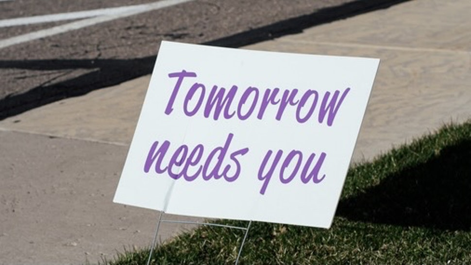 "Sign that reads ""Tomorrow needs you"" placed by a sidewalk. - stock photo"