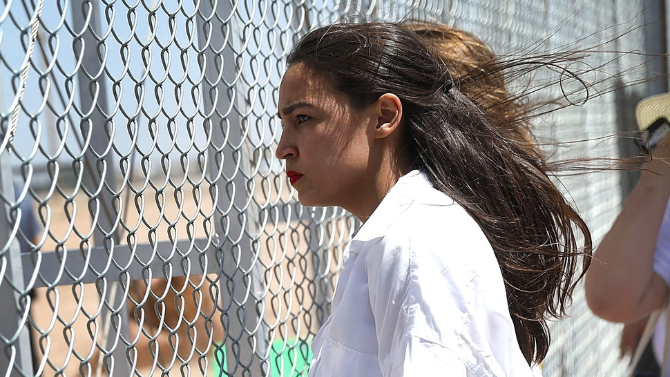 TORNILLO, TX - JUNE 24: Alexandria Ocasio-Cortez stands at the Tornillo-Guadalupe port of entry gate on June 24, 2018 in Tornillo, Texas. She is part of a group protesting the separation of children from their parents after they were caught entering the U.S. under the administration's zero tolerance policy.
