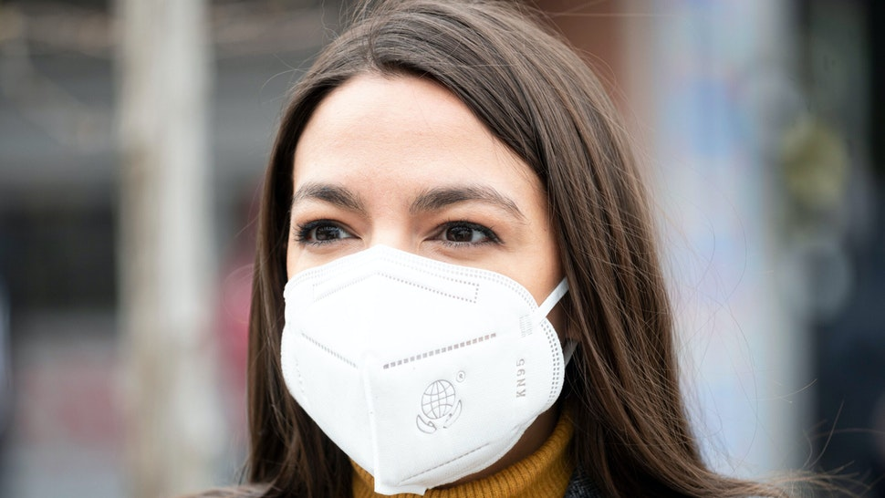 Democratic Congresswoman from New York Alexandria Ocasio-Cortez wears a face mask to protect herself from the coronavirus, during a press conference in the Corona neighbourhood of Queens on April 14, 2020 in New York City. - Senate Minority Leader Chuck Schumer and Democratic Rep. Alexandria Ocasio-Cortez hold a press conference amid the coronavirus pandemic to call on the Federal Emergency Management Administration (FEMA) to begin approving disaster funds to help families in lower-income communities and communities of color pay for funeral costs.