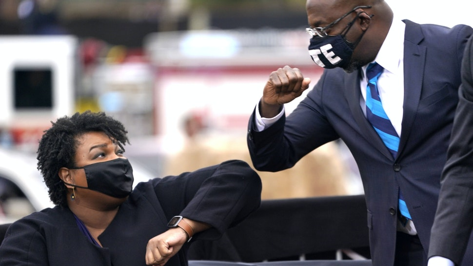 ATLANTA, GA - DECEMBER 15: U.S. Democratic Senate candidate Raphael Warnock (R) bumps elbows with Stacey Abrams (L) during a campaign rally with U.S. President-elect Joe Biden at Pullman Yard on December 15, 2020 in Atlanta, Georgia. Biden's stop in Georgia comes less than a month before the January 5 runoff election for Senate candidates Jon Ossoff and Raphael Warnock as they try to unseat Republican incumbents Sen. David Perdue and Sen. Kelly Loeffler.