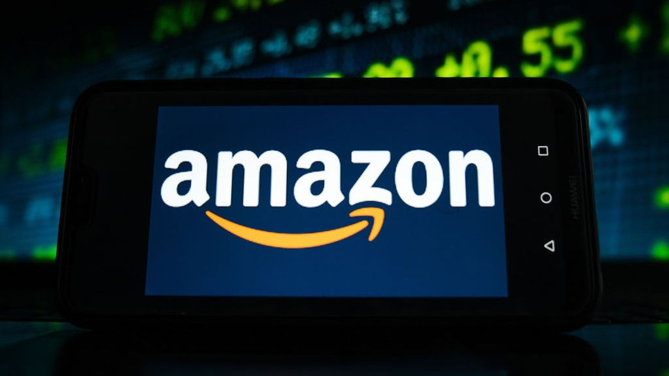 POLAND - 2021/02/05: In this photo illustration an Amazon logo seen displayed on a smartphone screen with stock market graphic on the background. (Photo Illustration by Omar Marques/SOPA Images/LightRocket via Getty Images)